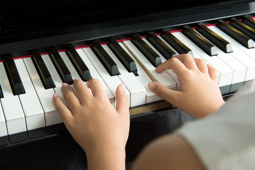 Close up of little girl playing music on piano